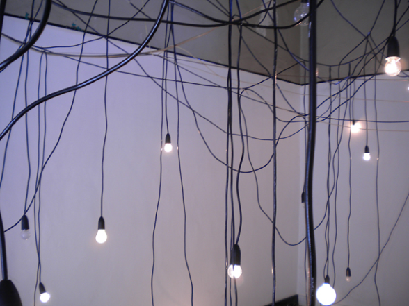 Image of a tangle of electrical cords and light bulbs hanging from the ceiling from the exhibition - Psychometropolis by Danielle Clej & Claire Robertson