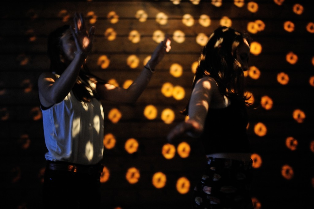 two girls dancing in a dark room with disco lighting