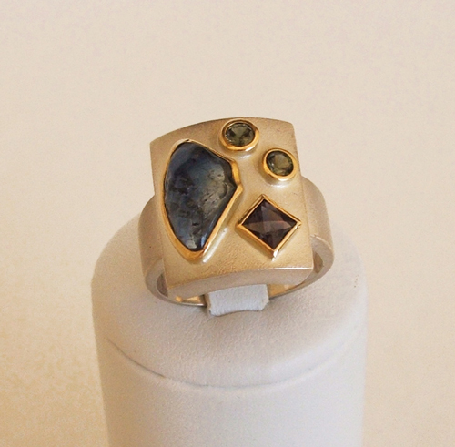 silver and yellow gold with green and balck sapphires
