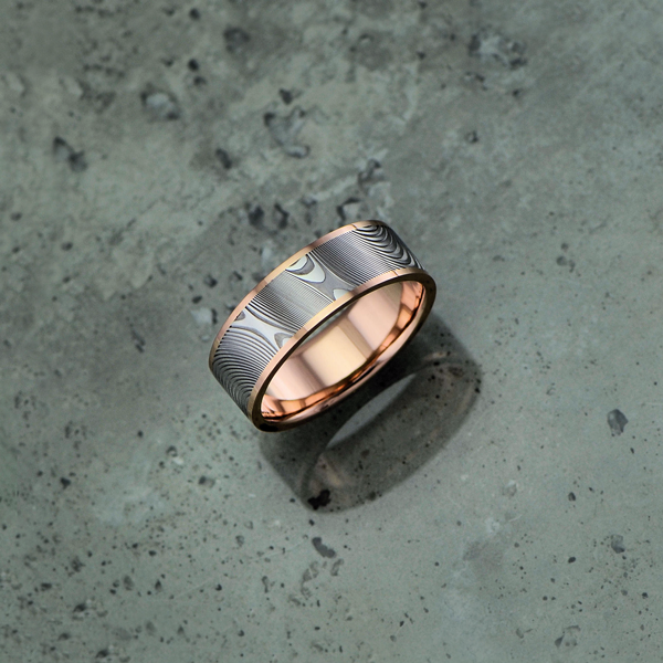 Image of Damascus steel ring with an 18ct rose gold liner and rails