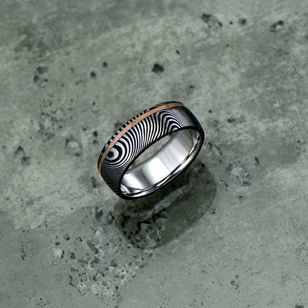 Image of Damascus steel ring with an 18ct rose gold off-centre inlay