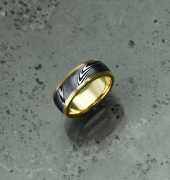 Image of Damascus steel ring with an 18ct yellow gold liner and rails