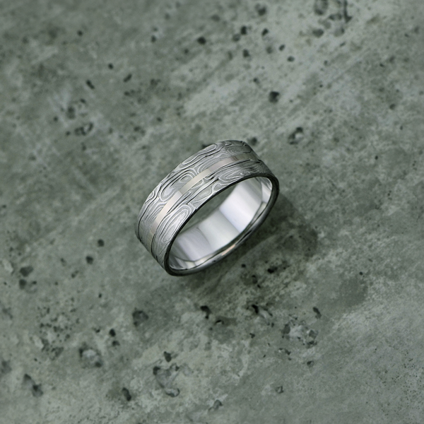 Image of custom patterned Damascus steel ring with an 18ct white gold central inlay