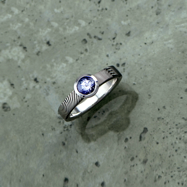 Image of custom engagement ring with Damascus steel shoulders, 18ct white gold band and bezel setting with light purple sapphire