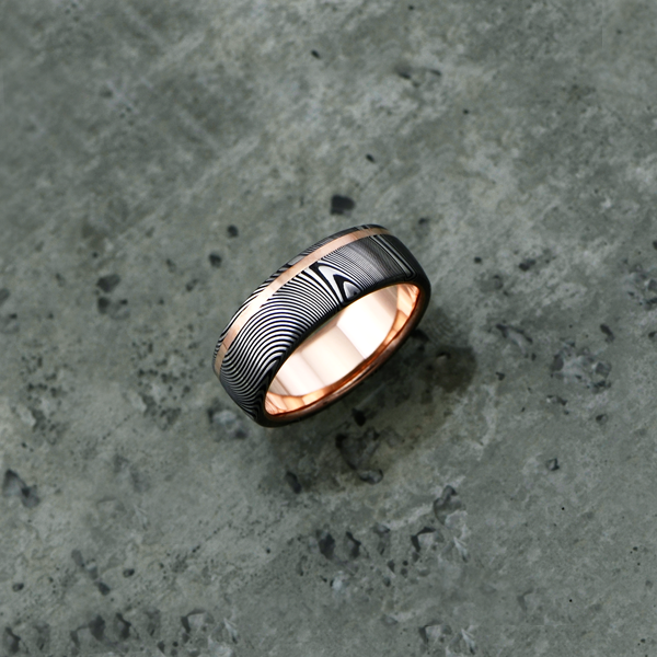 Image of Damascus steel ring with an 18ct rose gold off-centre inlay and liner