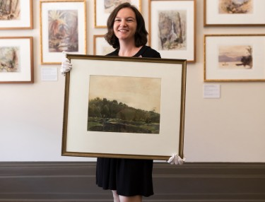 Dr Amy Jackett holding John Eldershaw watercolour Under the Hill