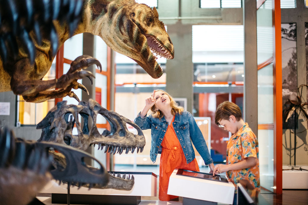 Two kids looking at a dinosaur in a Museum